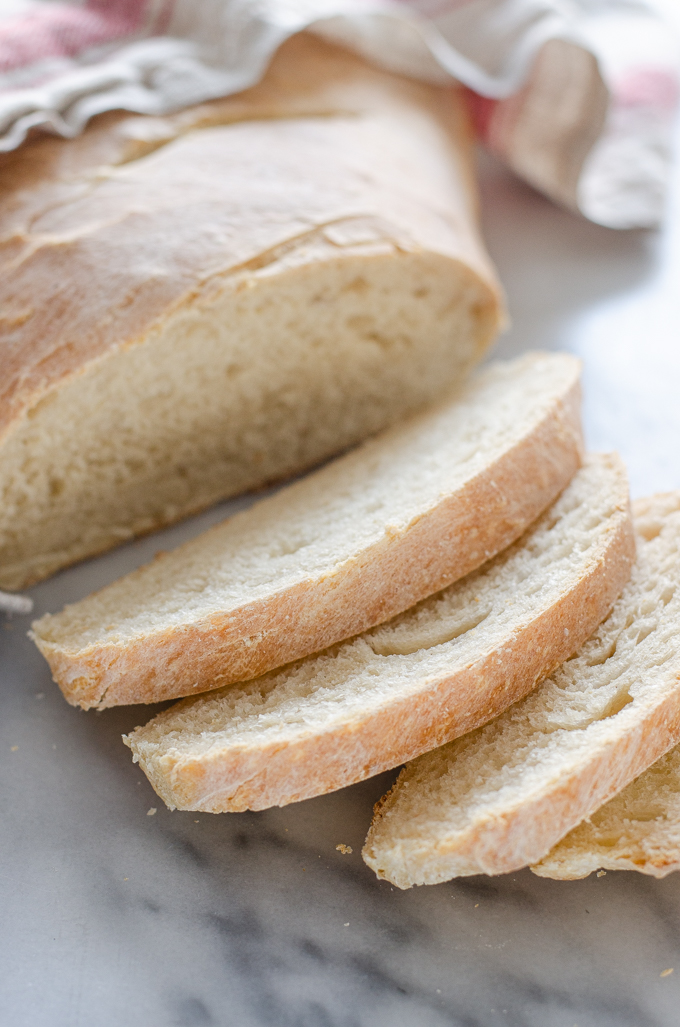A sliced loaf of Soft Sourdough French Bread No Yeast on a marble surface.
