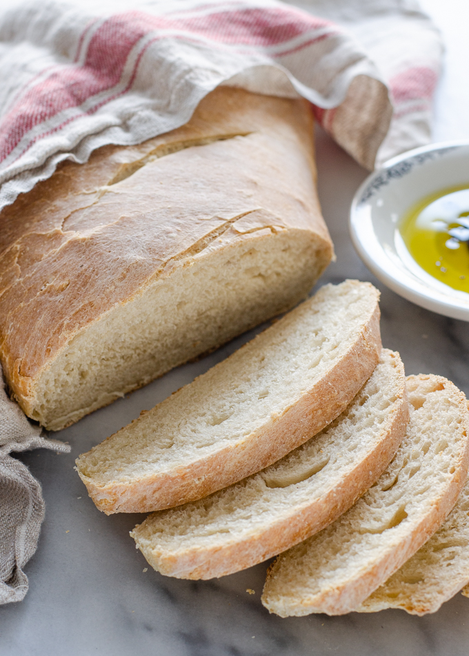 A sliced loaf of Soft Sourdough French Bread No Yeast all baked with a dish of olive oil and vinegar in the background.
