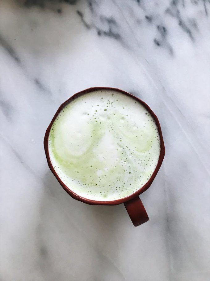 A mug of matcha latte on a marble surface.