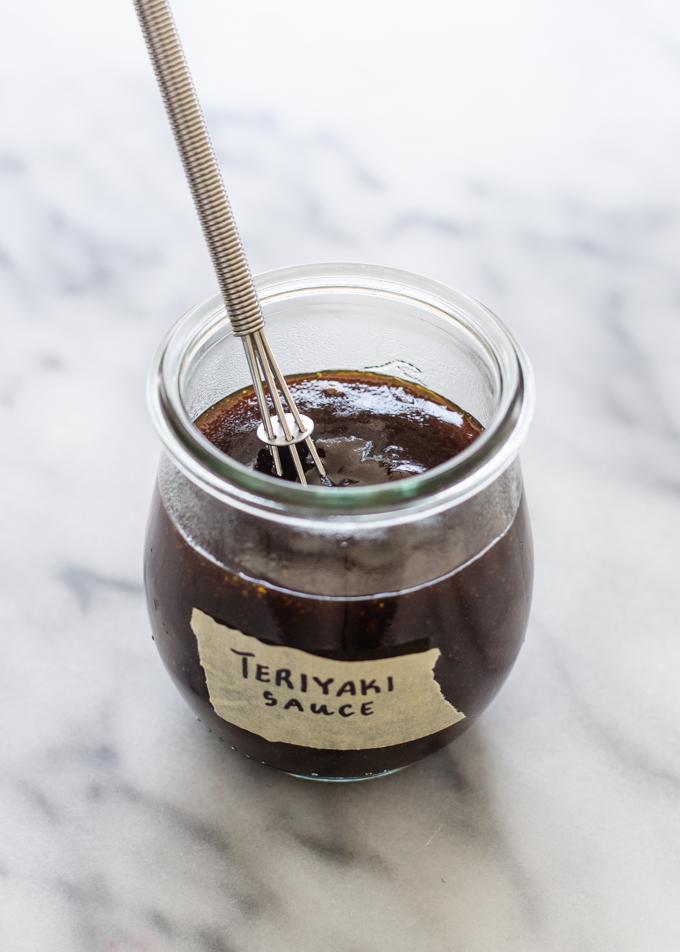 Homemade Teriyaki sauce in a small jar on a marble surface.
