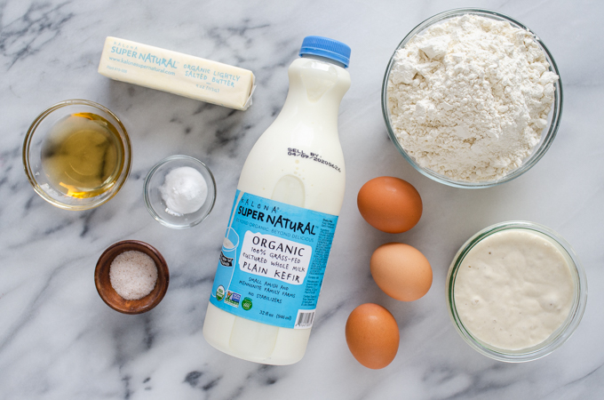 All of the ingredients for sourdough pancakes laid out on a marble surface.