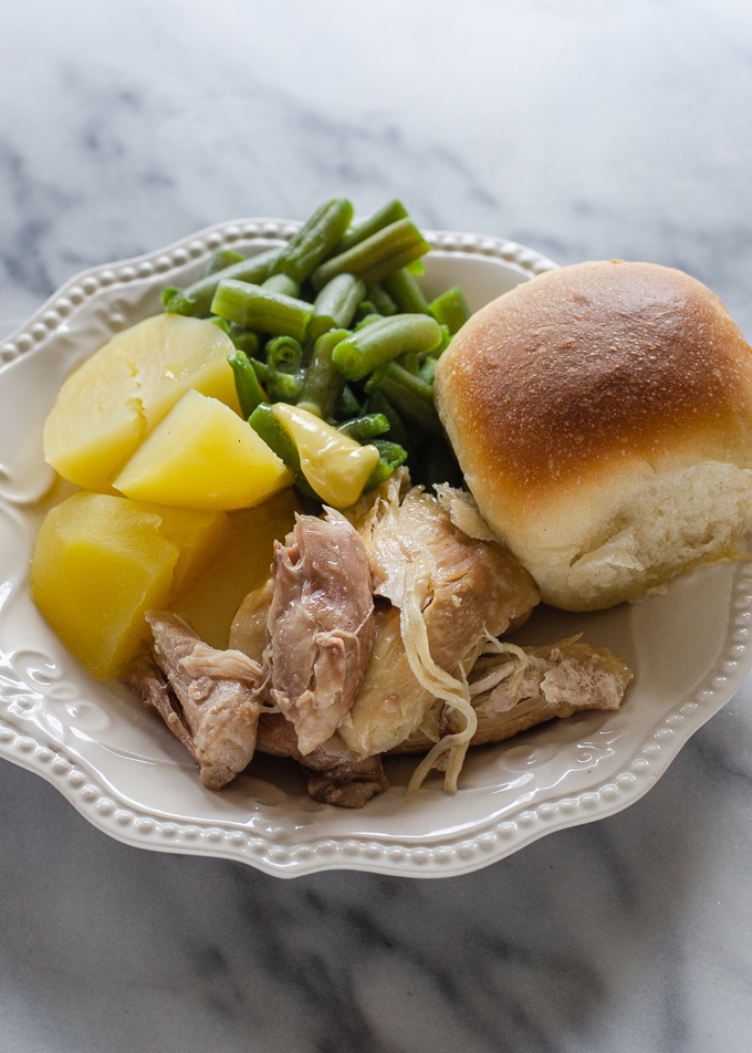 A plate filled with Instant Pot chicken, boiled yukon gold potatoes, green beans, and a sourdough roll.