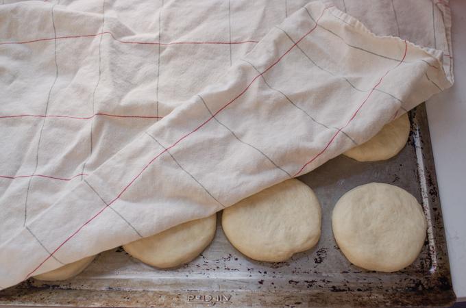 Covering the sourdough hamburger buns with a tea towel.