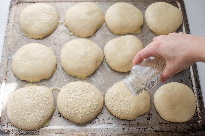 Sprinkling the buns with sesame seeds.