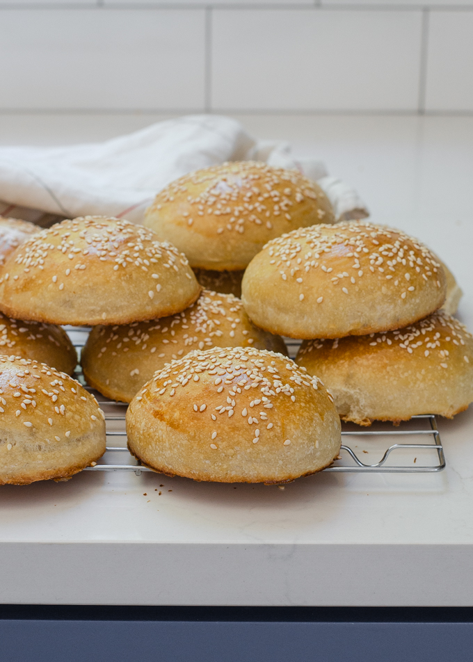 Sourdough hamburger buns on a cooling rack with a tea towel in the background.