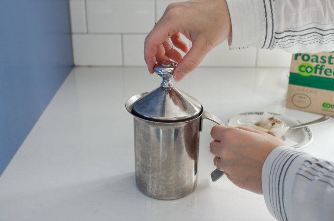 Frothing the milk with the hand pump milk frother.