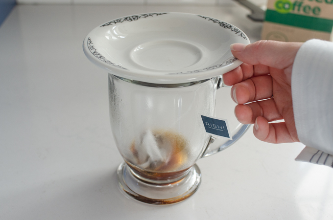 Putting a plate on the mug to retain the heat while the tea steeps.