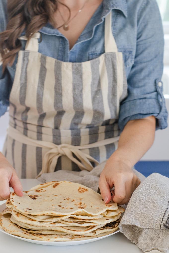 Placing the sourdough tortillas on a plate.
