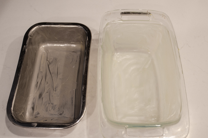Greasing two loaf pans: one stainless steel, and the other glass.