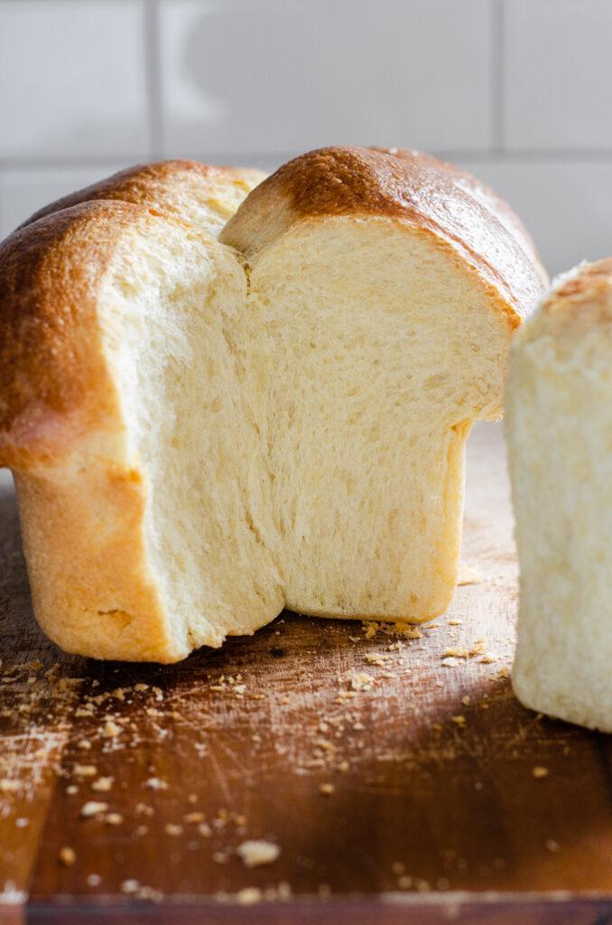 Sourdough brioche bun bread with a section taken out.