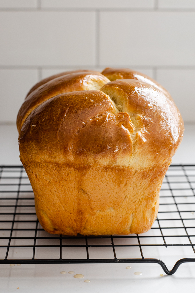 A loaf of sourdough brioche bread on a black wire cooling rack.