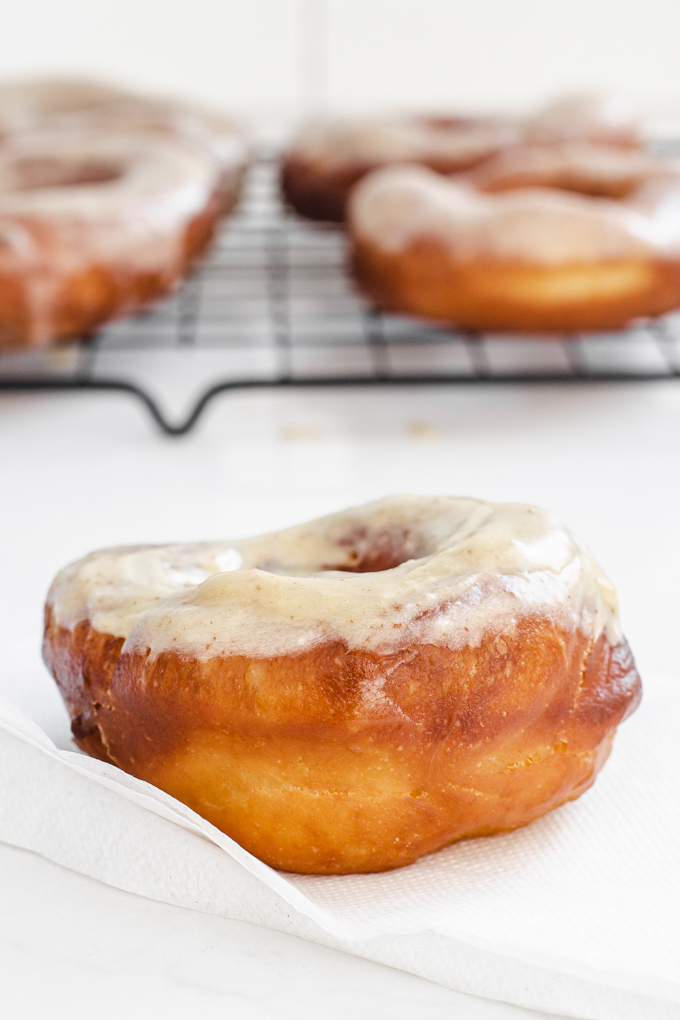 A donut on a napkin with more sourdough donuts on a wire cooling rack in the background.
