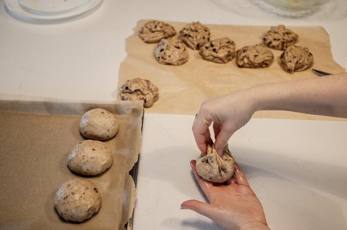 Pinching the corners of the sourdough hot cross buns dough ball.