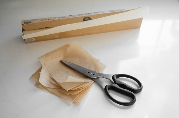 Cutting out squares of parchment paper for sourdough English muffins.
