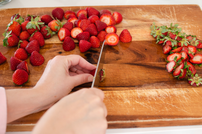Chopping strawberries on a wooden cutting board.
