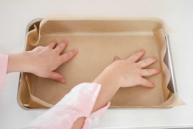 Lining a 13x9-inch baking pan with parchment paper.